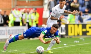 Leeds United's Ben White in action with Wigan Athletic's Kieffer Moore