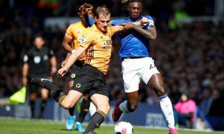 Wolverhampton Wanderers' Ryan Bennett in action with Everton's Moise Kean