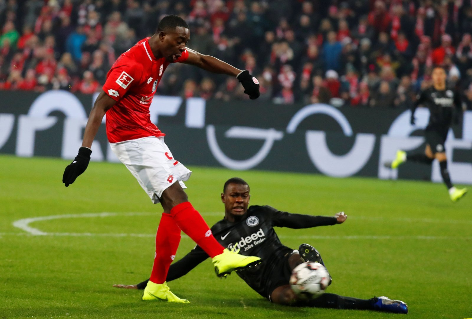 Mainz's Jean-Philippe Mateta shoots at goal as Eintracht Frankfurt's Evan N'Dicka challenges